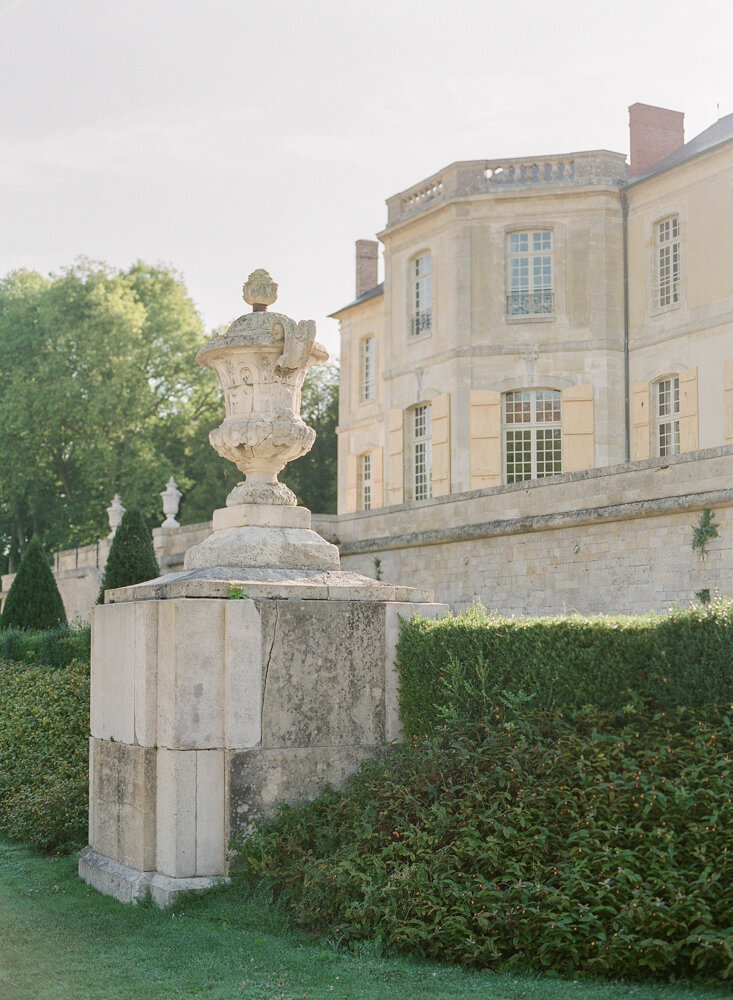 Large stone cream statue with off white chateau behind it