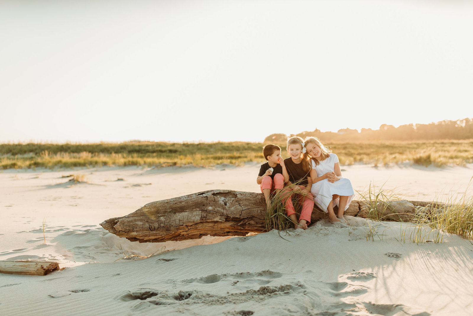 three siblings sit on beach rock and giggle during family portraits in boston
