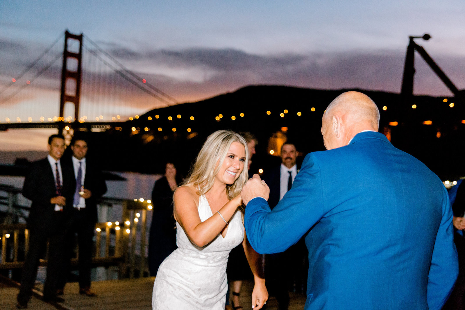 bride dancing with her Dad at sunset with the golden gate bridge in the background
