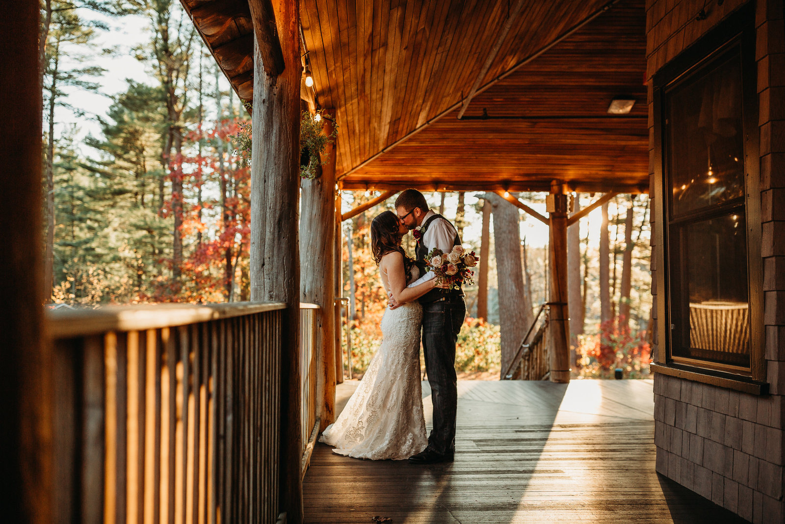 bride and groom kiss in golden light on outdoor porch