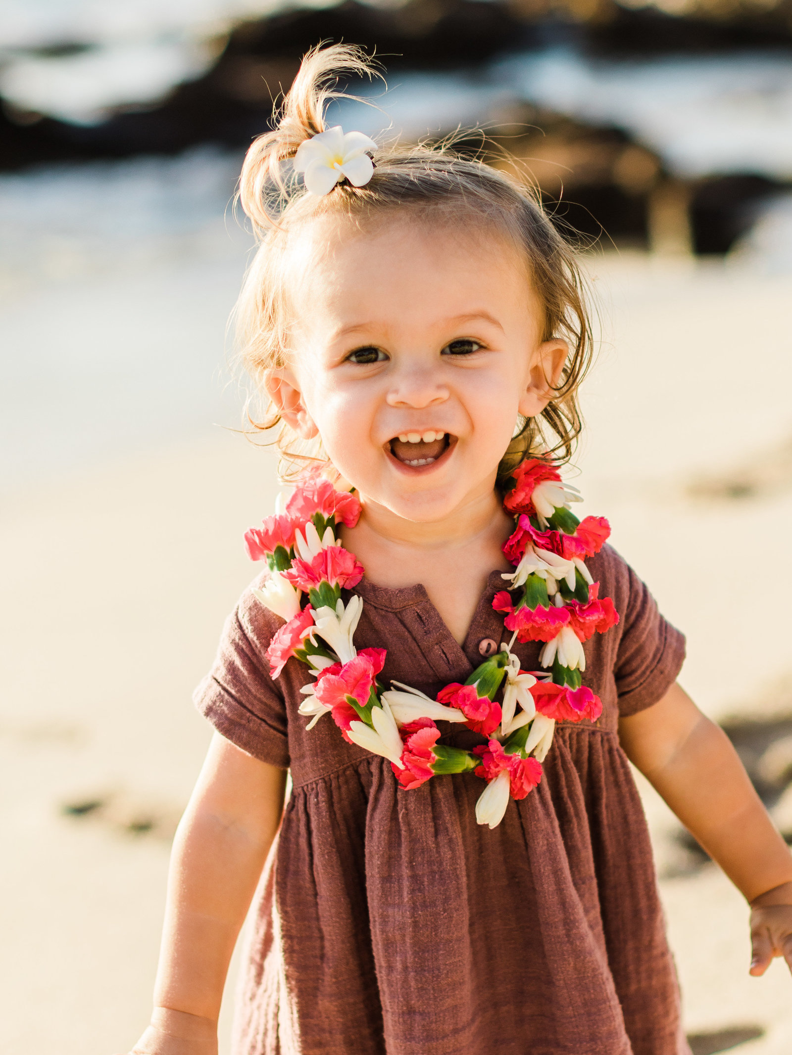 Toddler smiles at the camera while wearing a lei on a beach in hawaii