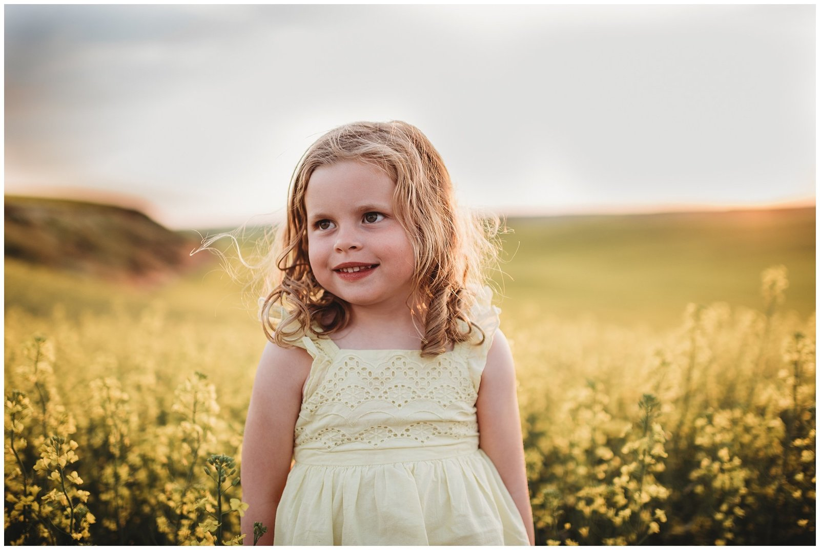 blonde curly hair girl in yellow dress in field of yellow flowers at sunset Emily Ann Photography Seattle Family Photographer