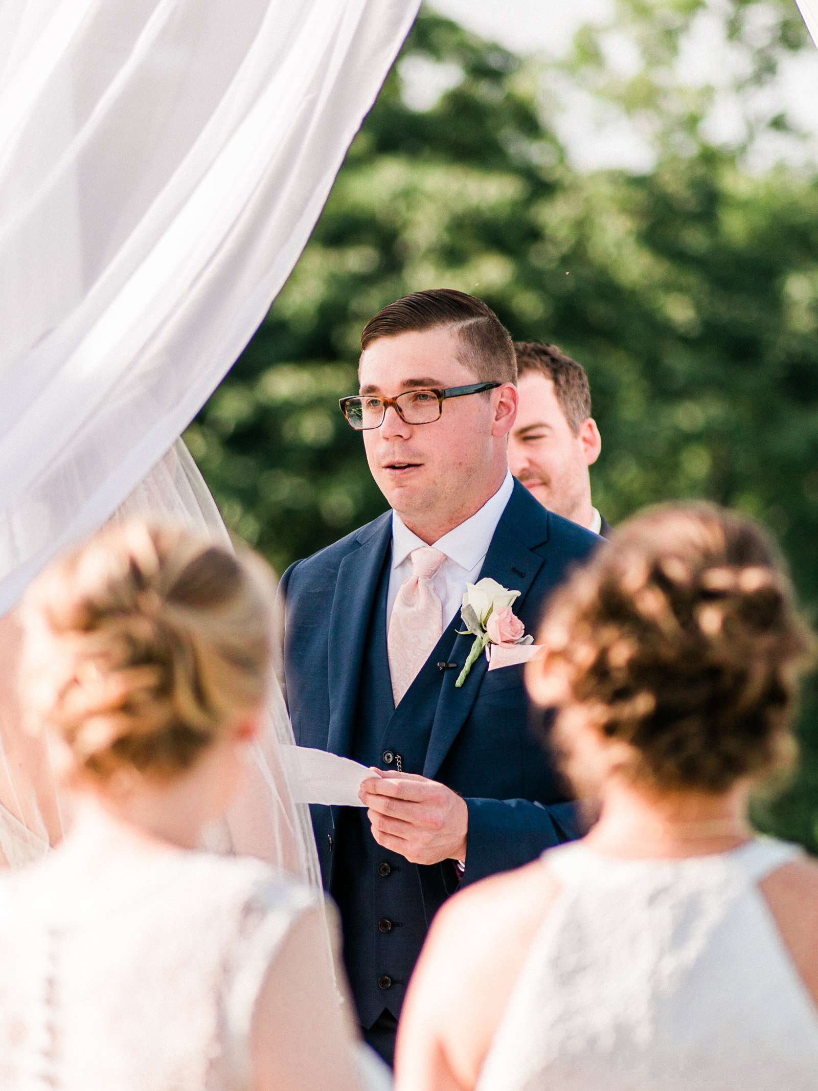 Groom reads his vow to his bride in their ceremony