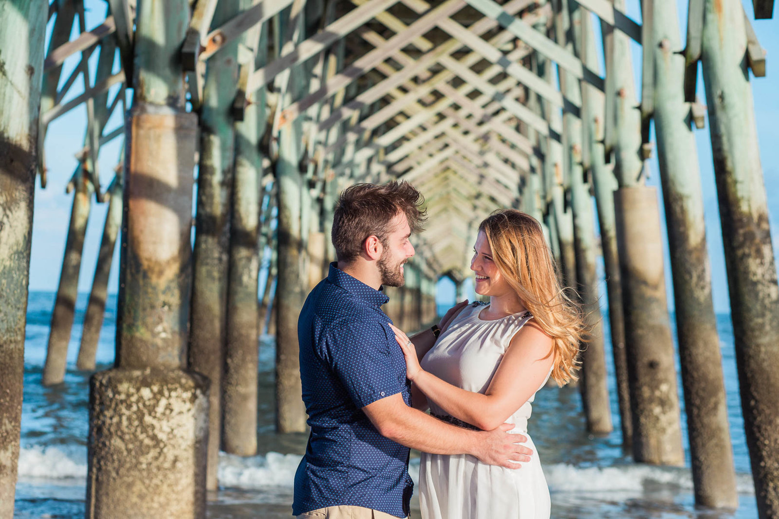 Engaged Couple hugging under fishing pier, Folly beach in Charleston, South Carolina