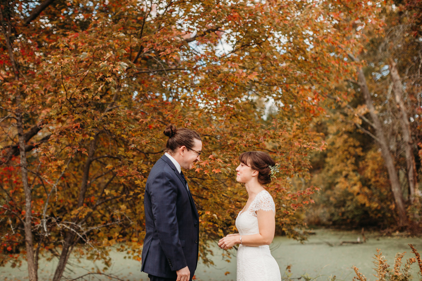 bride and groom look at eachother outdoors by autumn foliage in boston mass