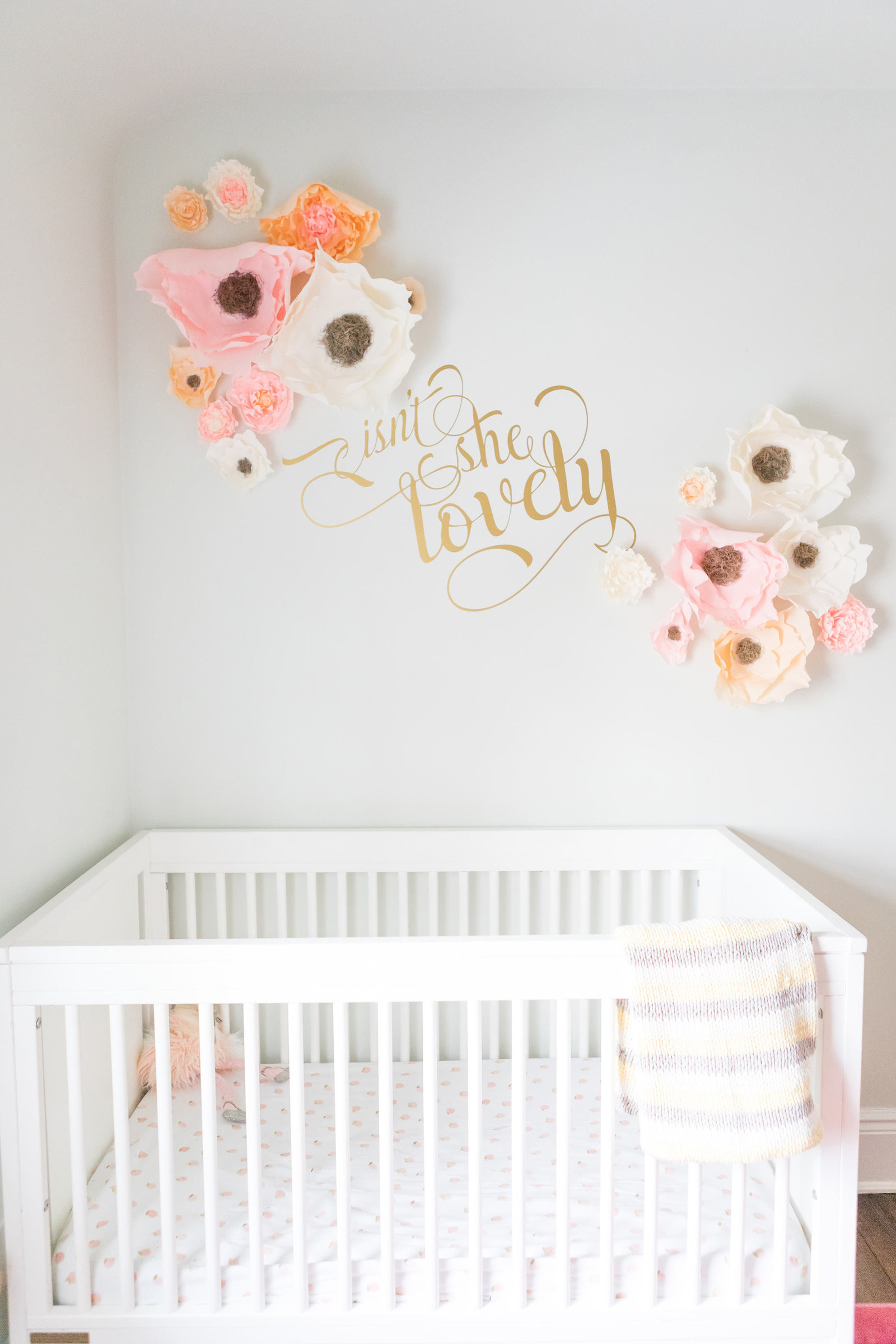 A crib with 3D paper flowers and gold quote.
