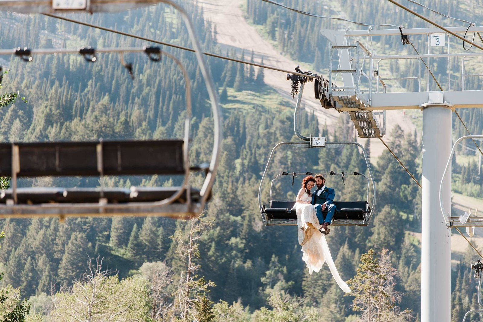 Jackson Hole adventure elopement photographer Amy Galbraith's image of a bride and groom on a chairlift at Jackson Hole Mountain Resort
