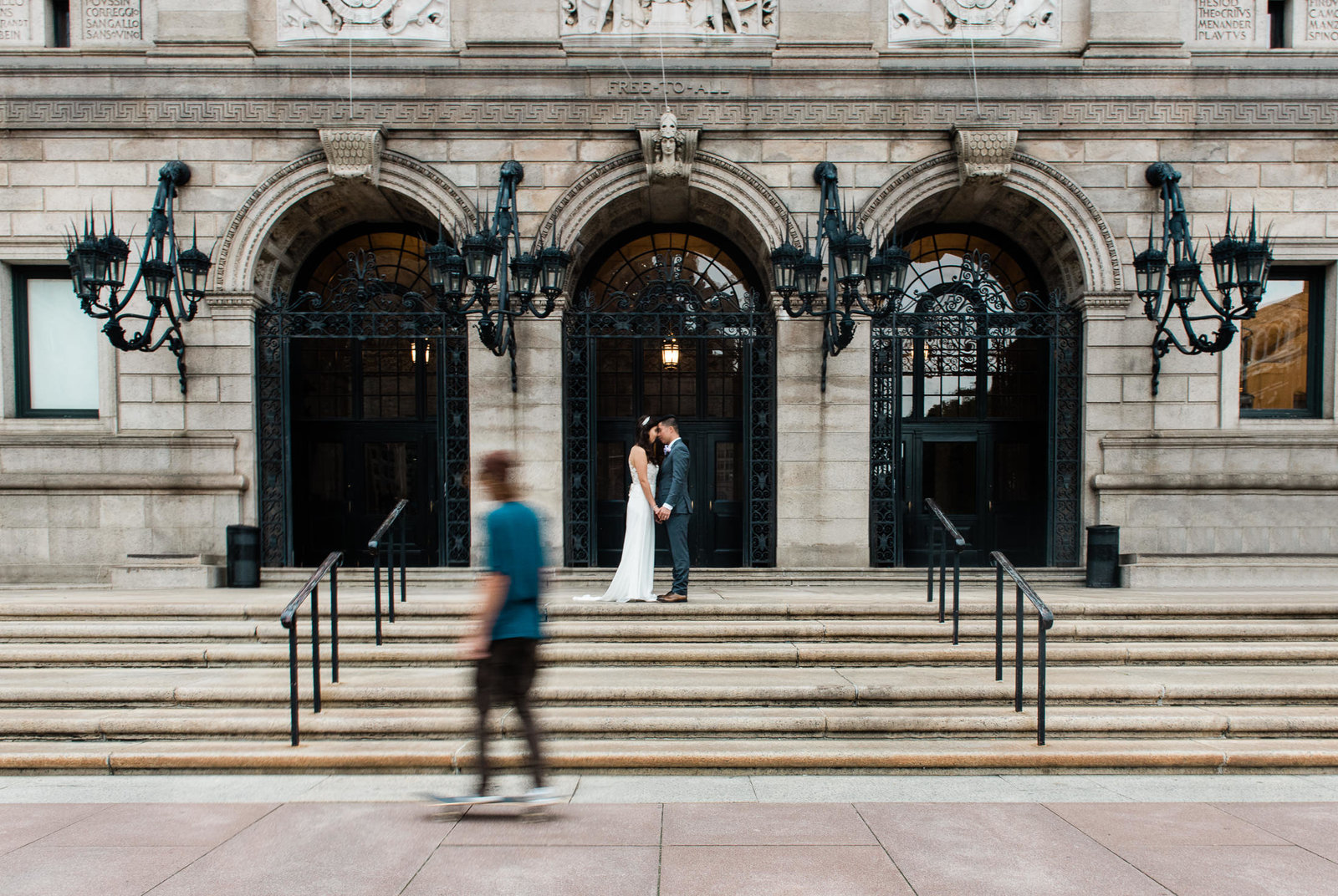 A couple kisses on the steps at their Boston Public Library wedding in downtown Boston