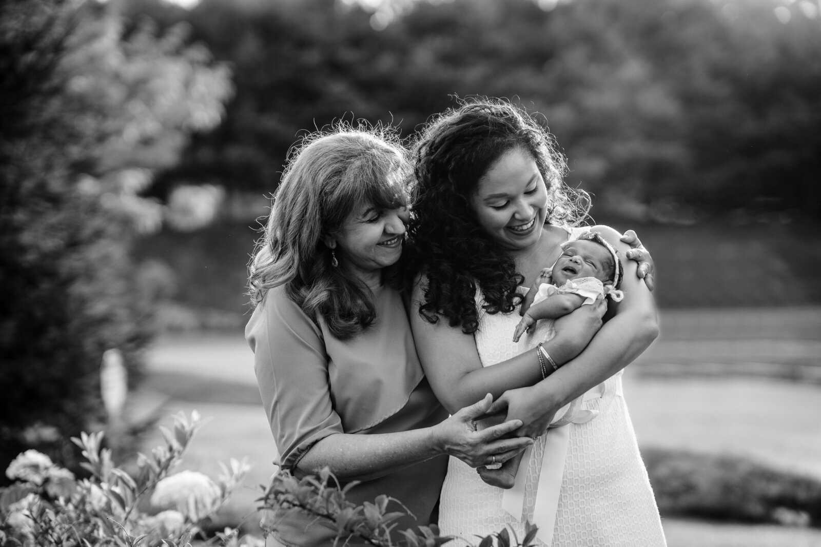 grandmother and mother hold newborn baby girl in generational portrait