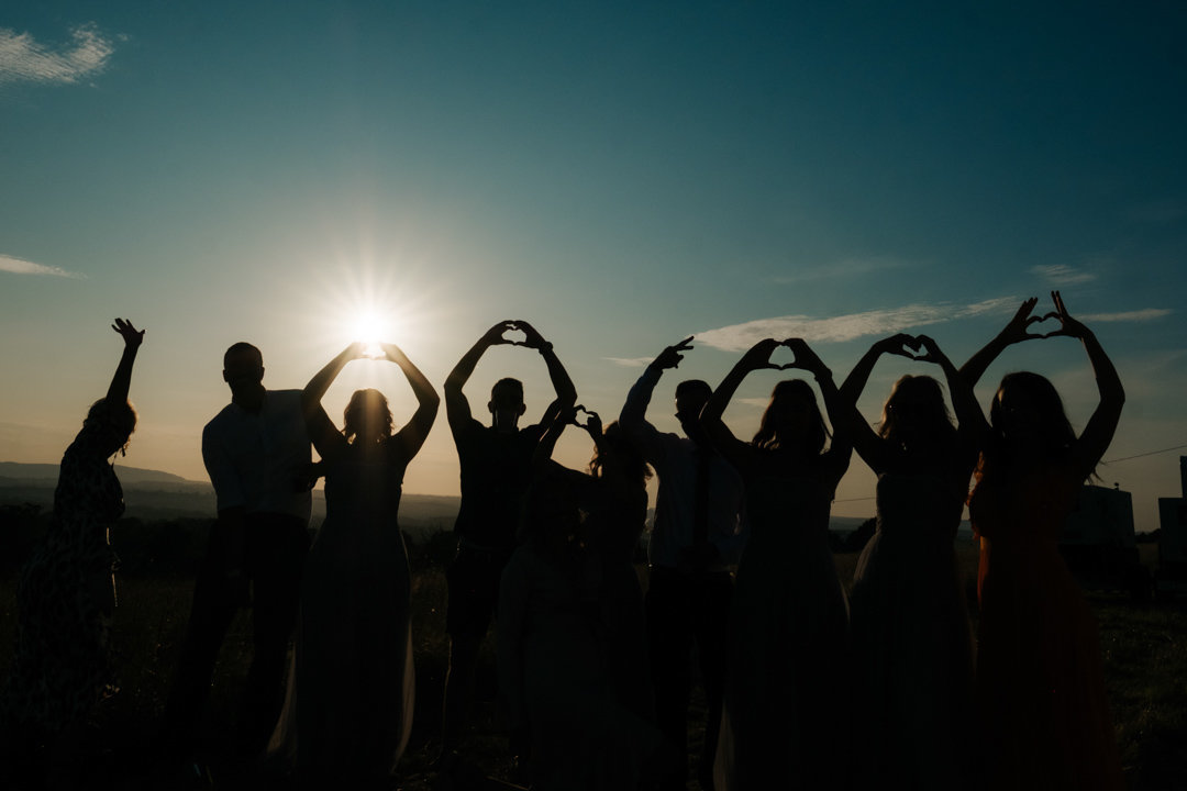 9 wedding guests make heats and shapes with their hands in this silhouette photograph in front of the sunset at their friends wedding