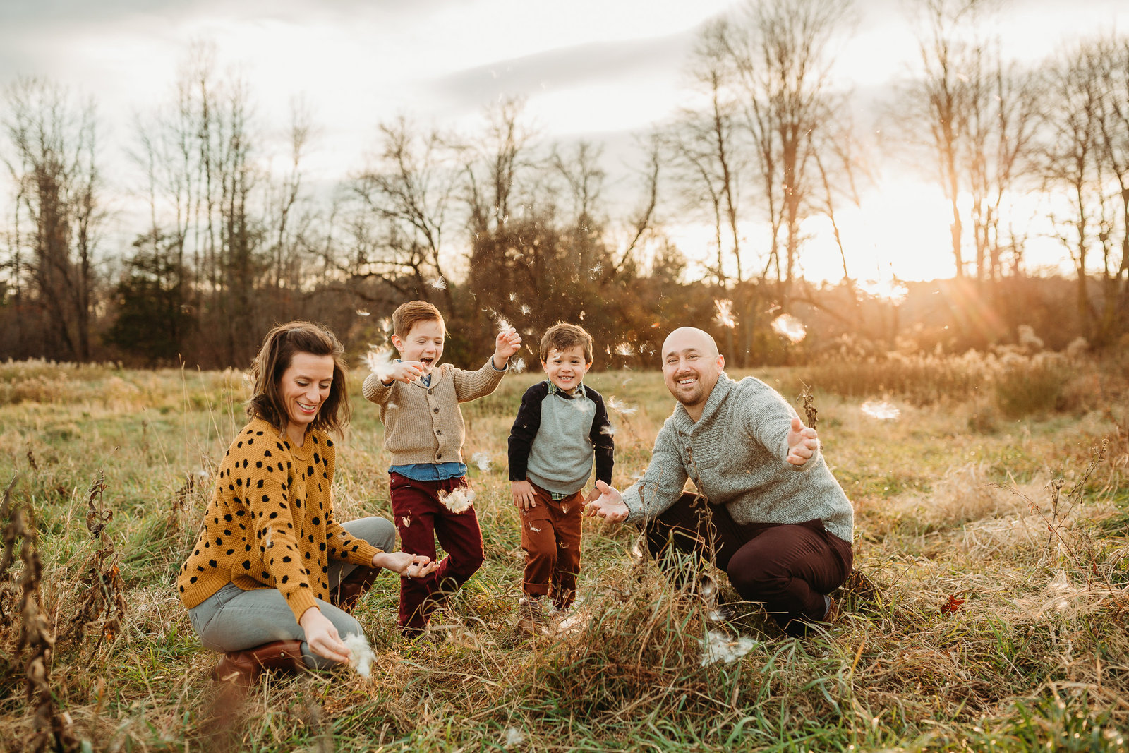 family of four throw milkweed in air during sunset family session in framingham ma