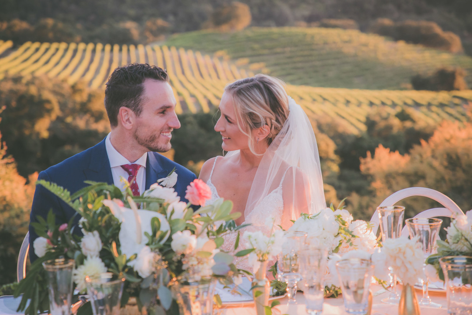 Bride and groom smile at each other during sunset at a vineyard in Carmel.