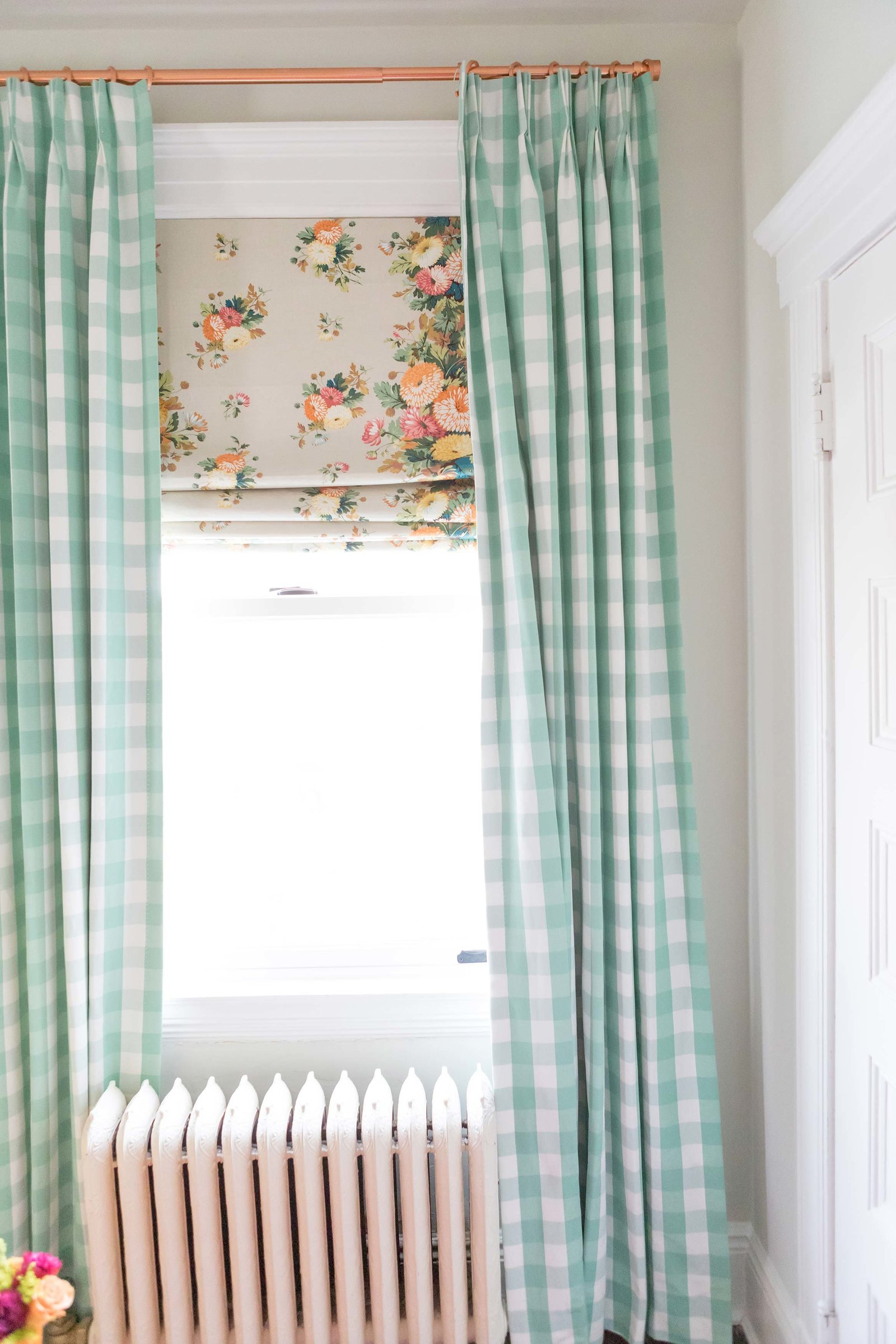 Mint gingham and floral curtains in a nursery.