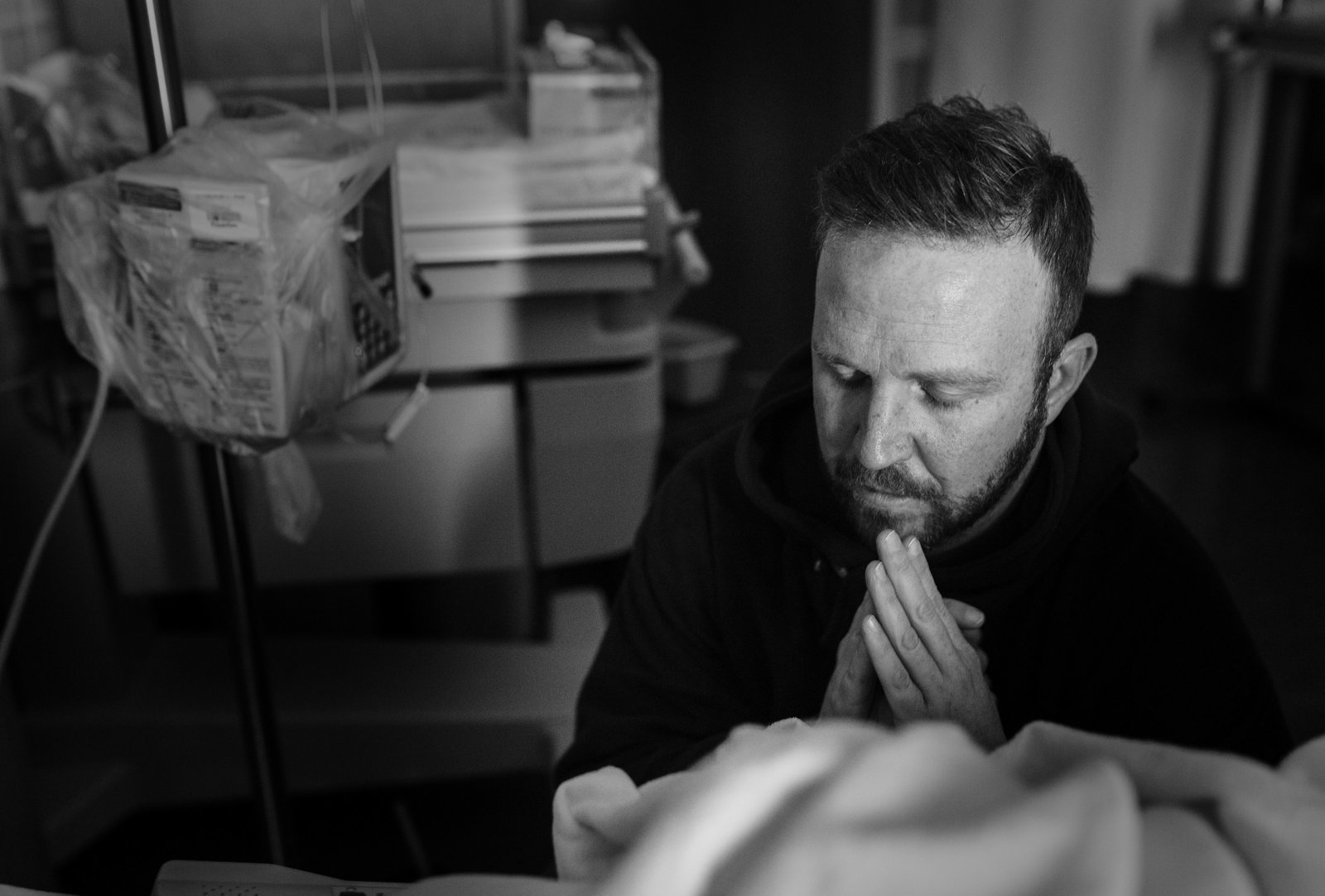 charlotte birth photographer jamie lucido captures a dramatic image of a father praying at his wife's bedside during the birth of their child