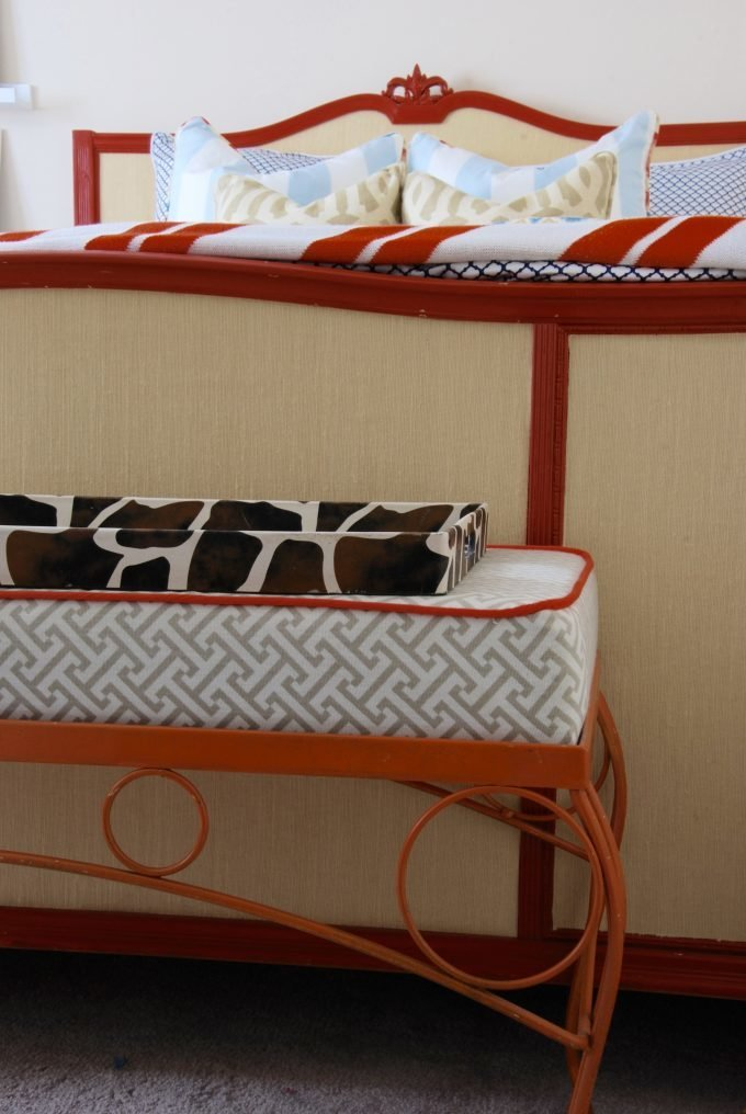 An orange iron bench in front of a footboard.