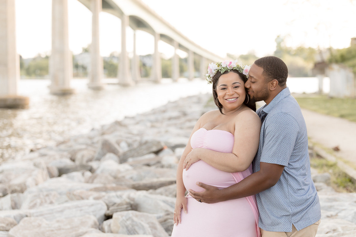 pregnant couple embraces underneath Annapolis bridge