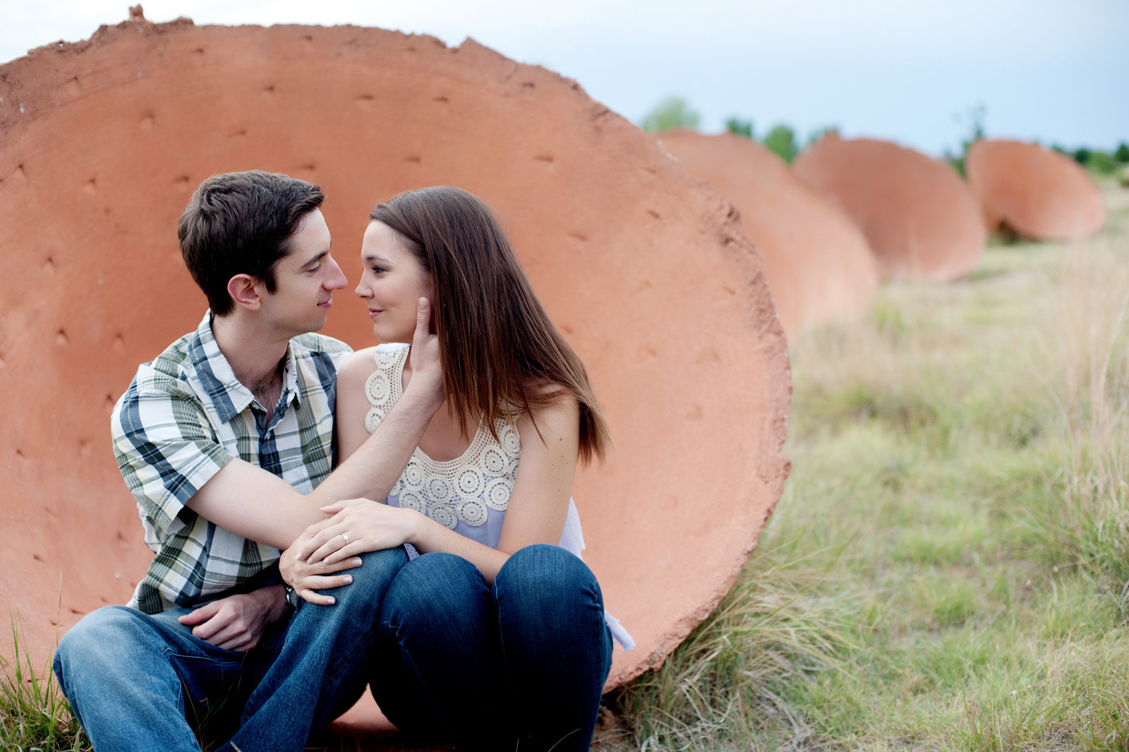 a man caresses his fiance's face as they sit in giant disc sculptures in denver