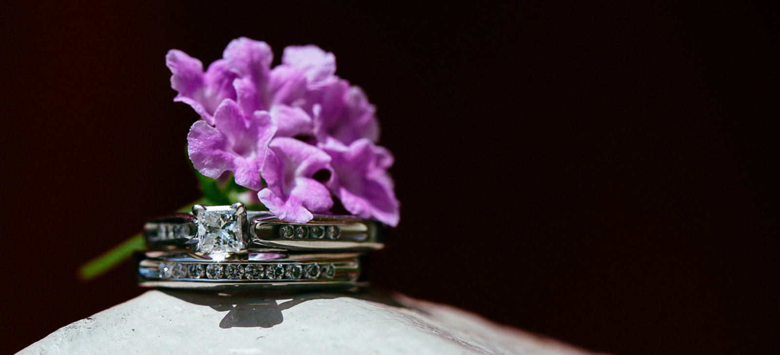 Close up of wedding rings with flower. Photo by Ross Photography, Trinidad, W.I..