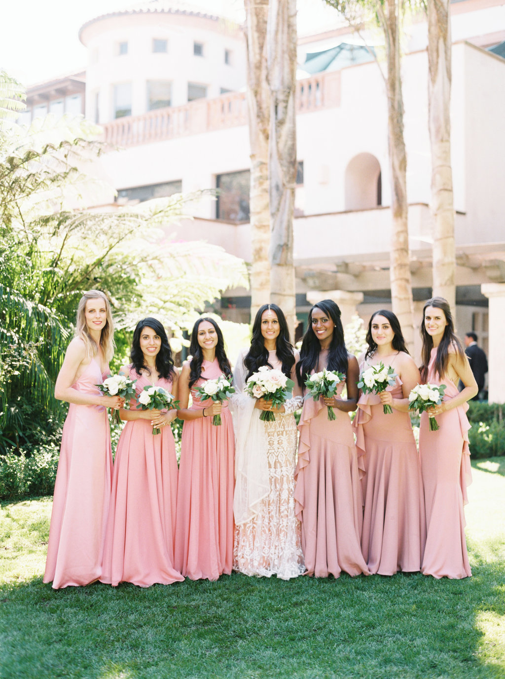 Bride and bridesmaids in pink dresses for wedding party photo at Butterfly Lane Estate