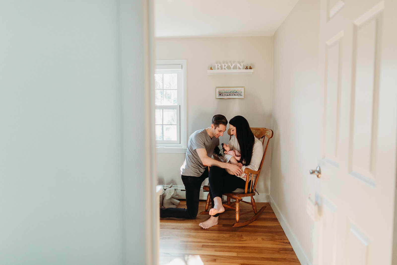 couple sits in rocking chair in white nursery with baby in south boston ma