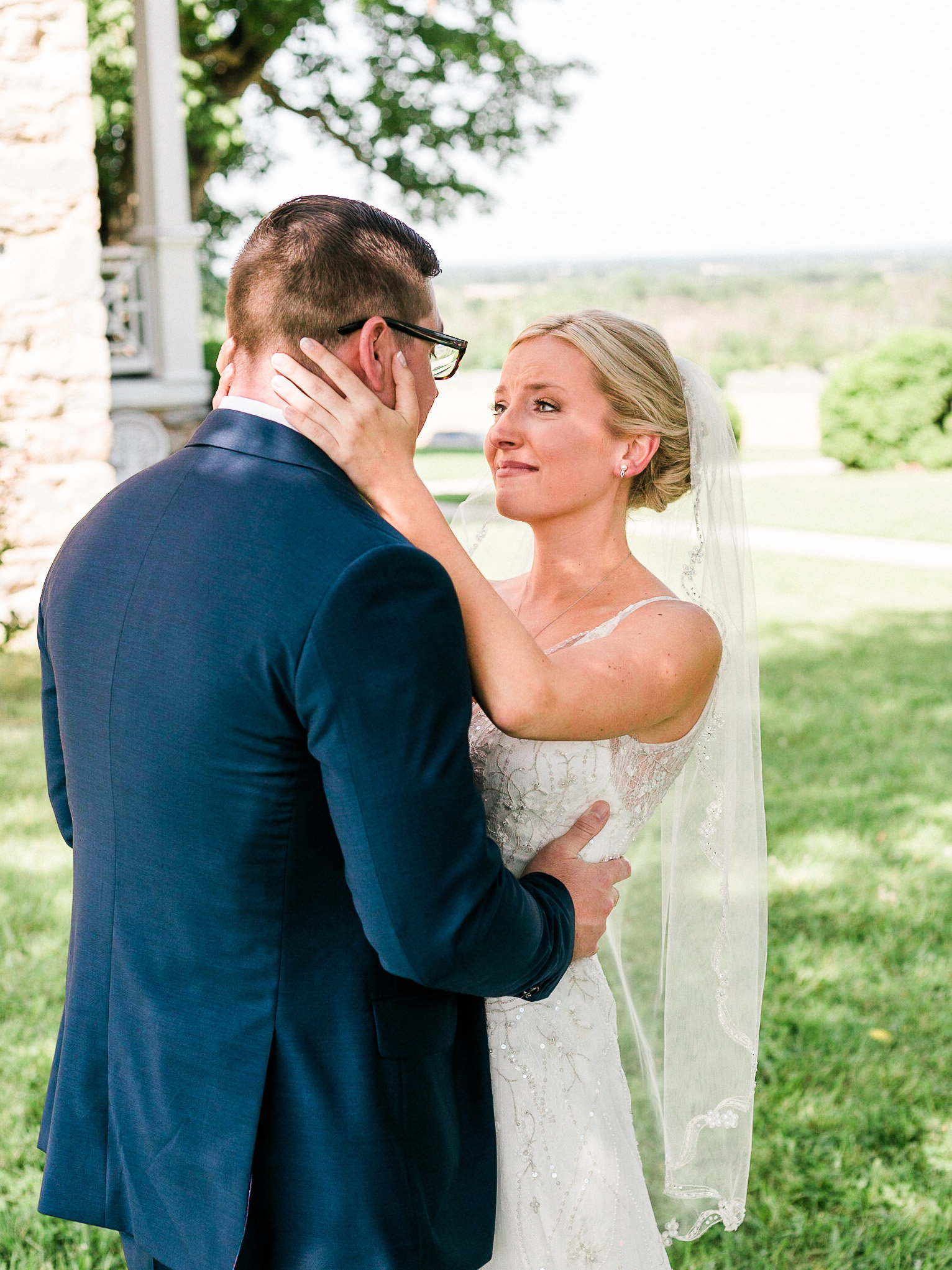 During a first look, a bride cries while smiling, holding her groom's head in her hands