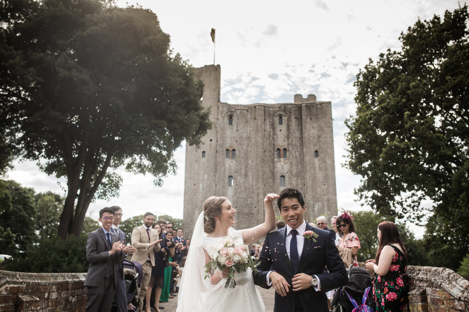 A bride wipes confetti off of her Groom's head as he looks to the camera and smiles. Hedingham castle and wedding guests are in the background.