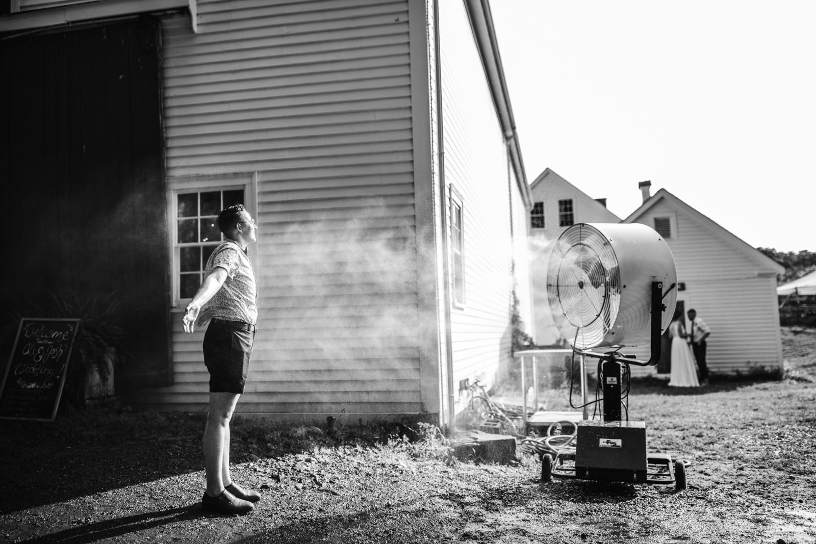 person stands in front of misting fan at a farm wedding