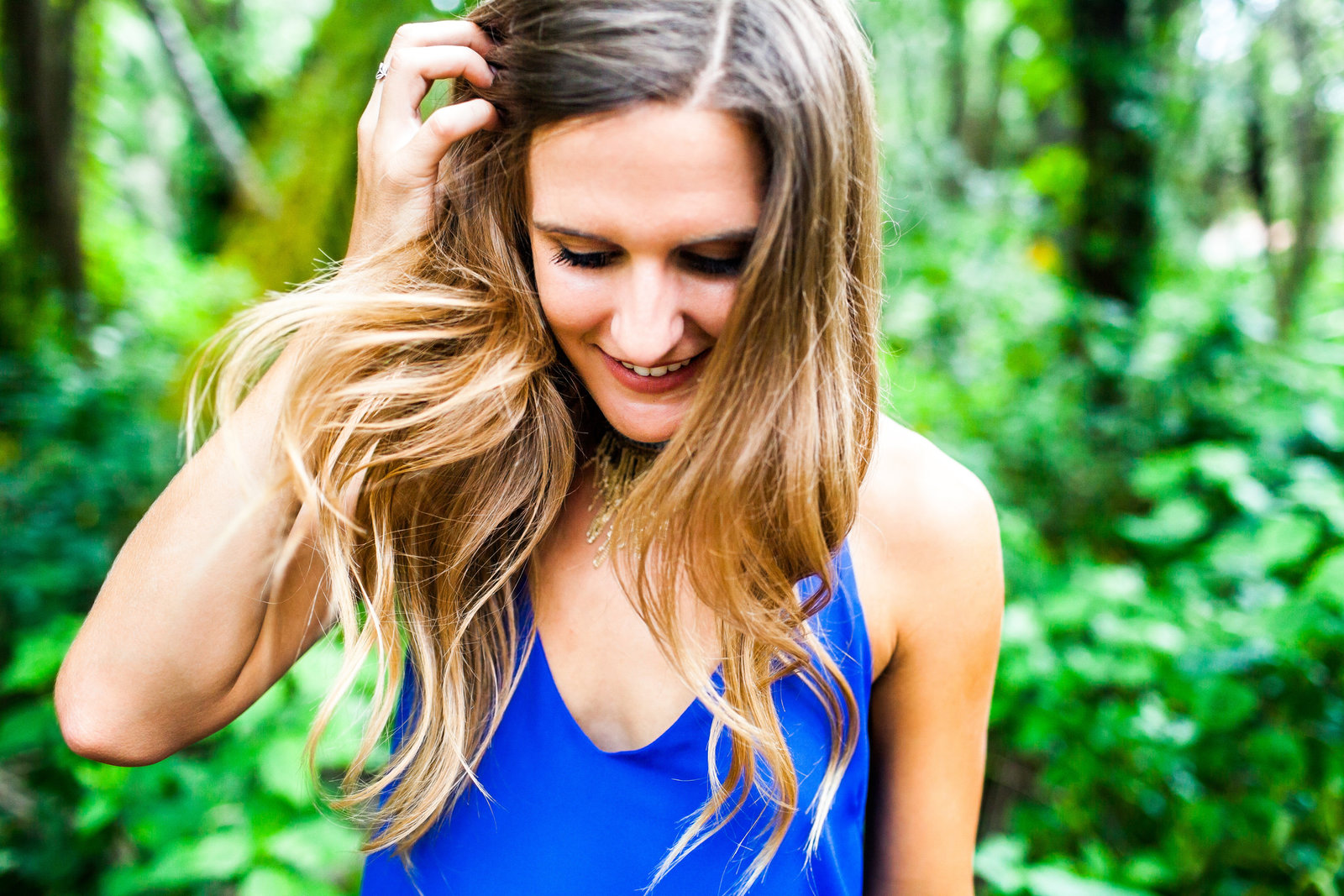 Hair blowing in the wind with lush greenery and blue dress