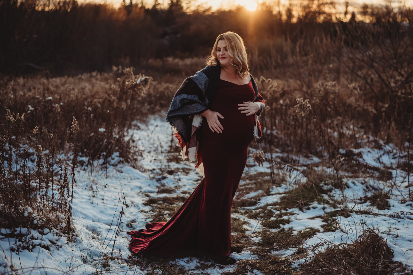 Pregnant women in a burgundy dress at sunset in Oshawa