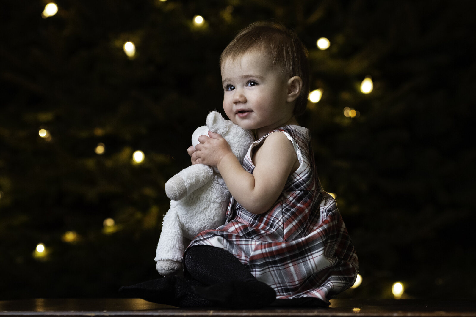 baby sitting for christmas photo in front of tree in nj portrait studio