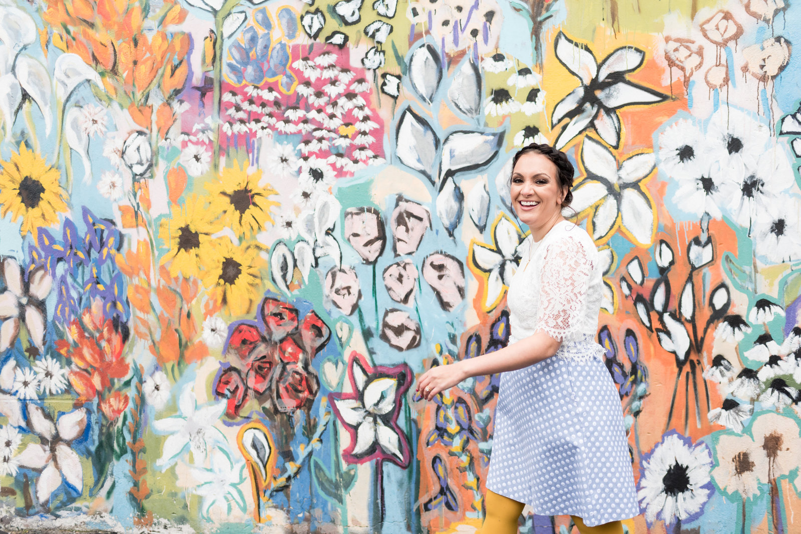 Joyful woman wearing a lace white top with blue dress is walking and smiling as she walks past a floral backdrop in 12th south