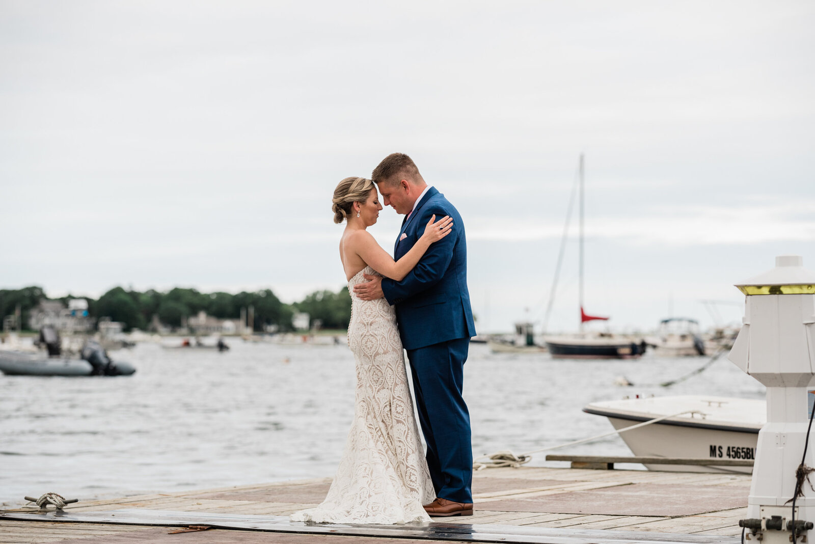 A couple shares a moment after their first look on the dock at their Duxbury Bay Maritime School Wedding