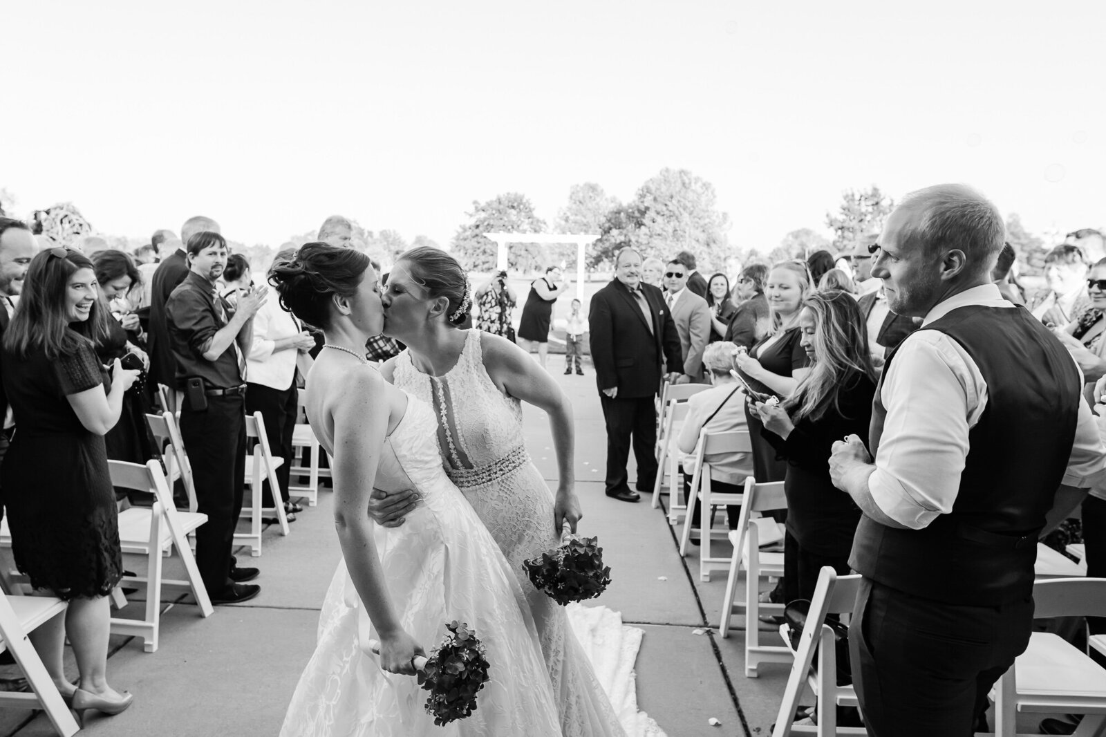 Two brides kiss after walking down the aisle after their Forest Park wedding ceremony in St. Louis