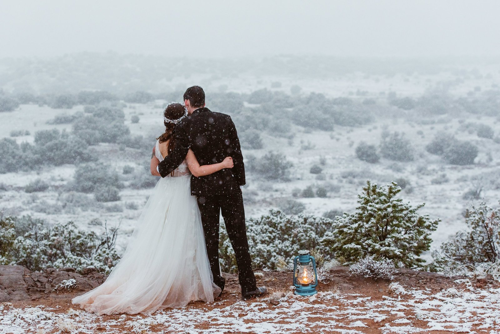 Adventurous couple looks out on snow covered desert for their New Mexico elopement