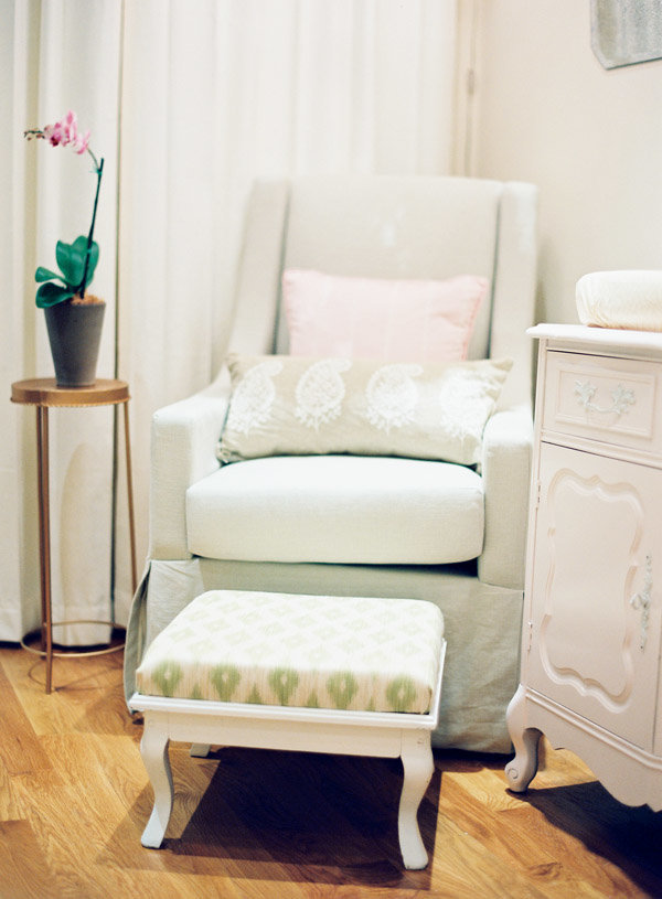 A light green rocking chair and foot stool in a nursery.