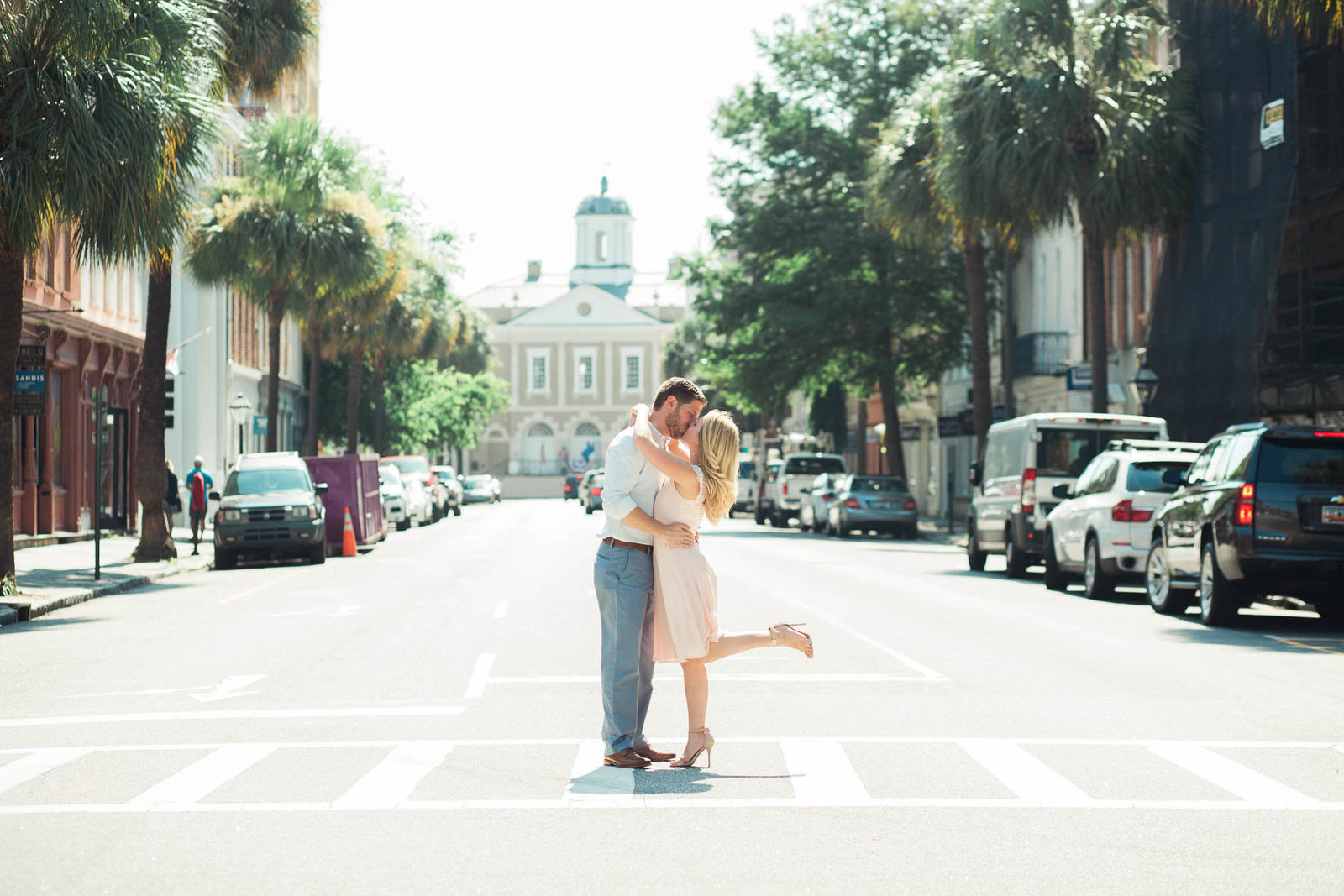 Engaged couple stops to kiss on Broad Street, Downtown Charleston, South Carolina