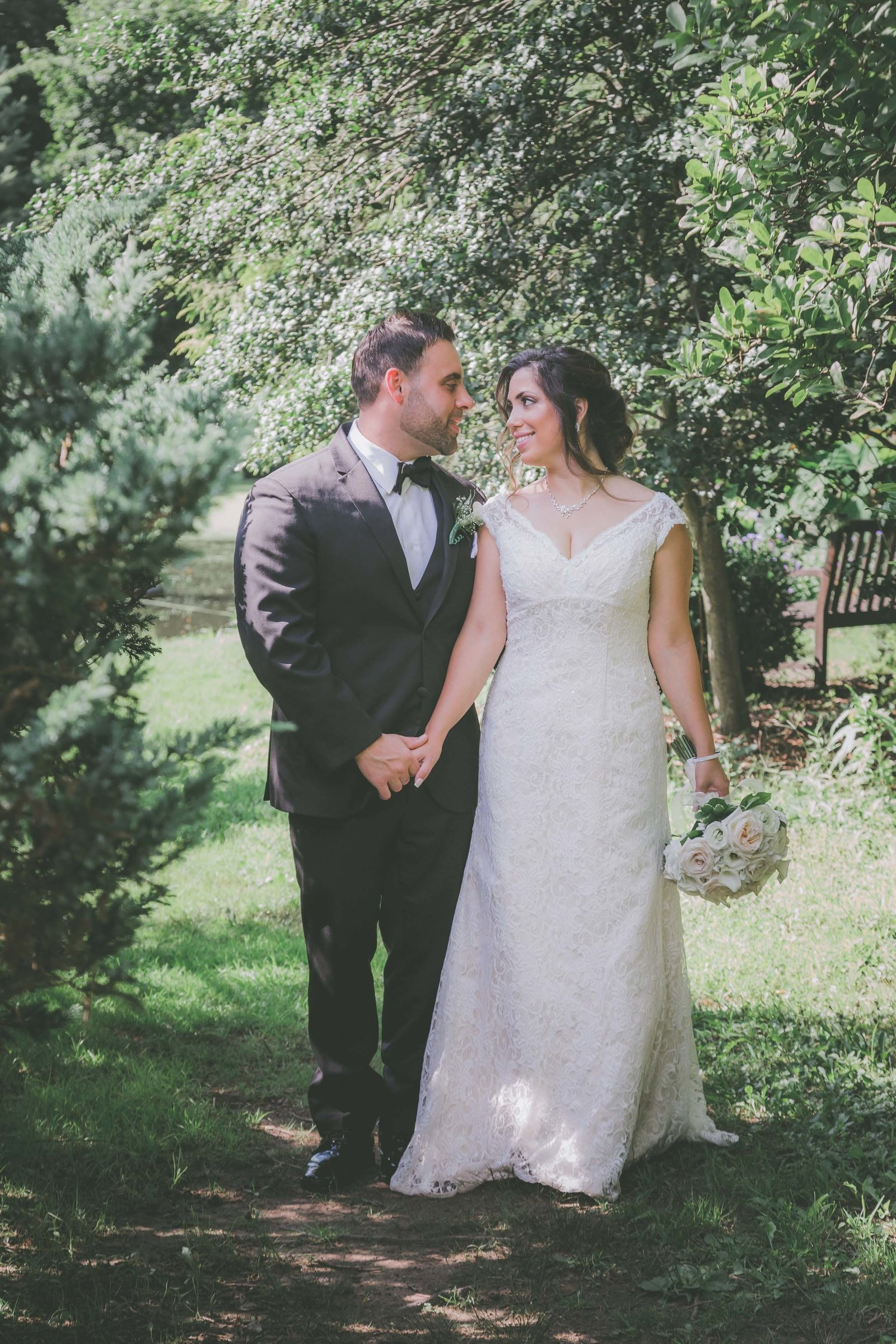 A couple hold hands and look at each other in a California garden for their elopement.