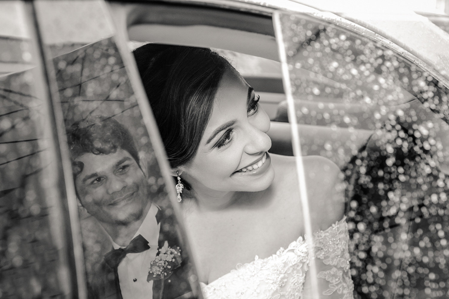 Bride in car with groom's reflection in B+W. Photo by Ross Photography, Trinidad, W.I..