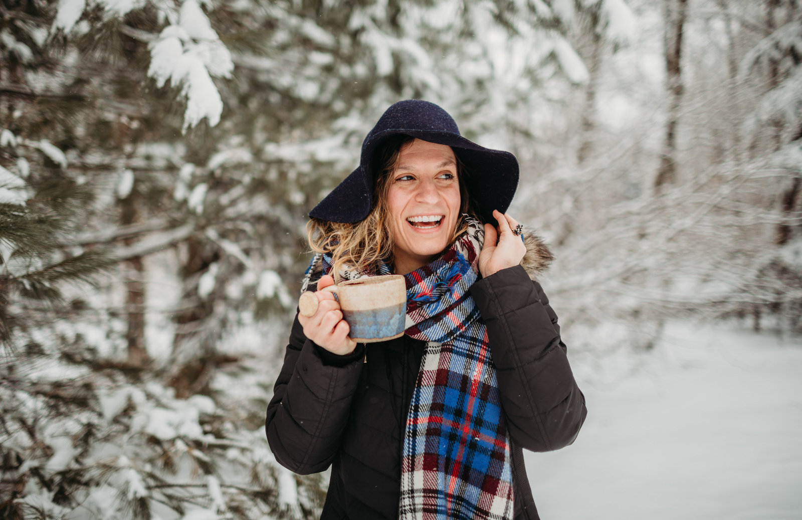 woman stands in snow with coffee mug and laughs during personal brand photos