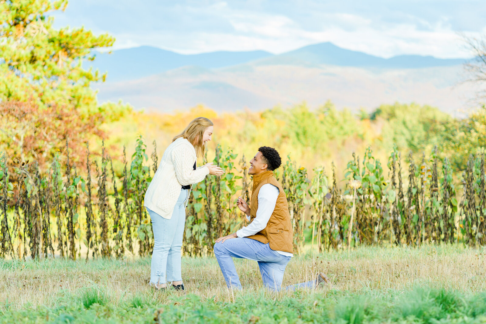 Man down on one knee proposing with New Hampshire mountains in background