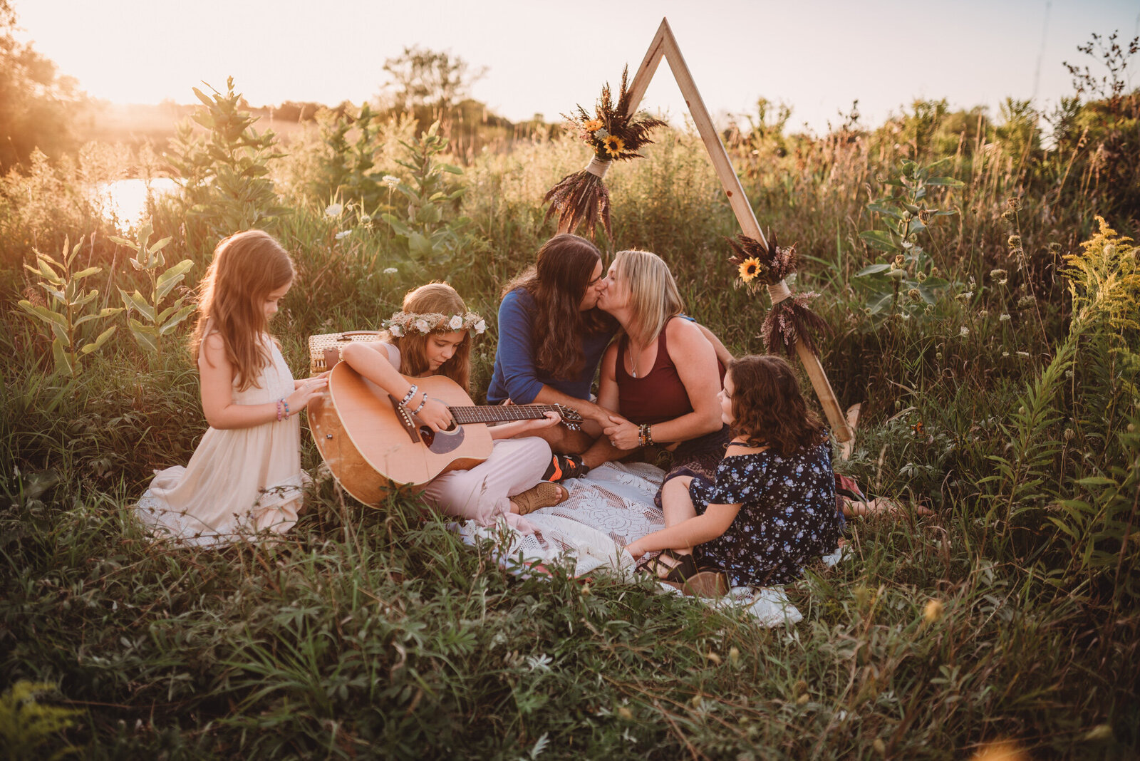Young girl playing guitar with her family in a field in Oshawa