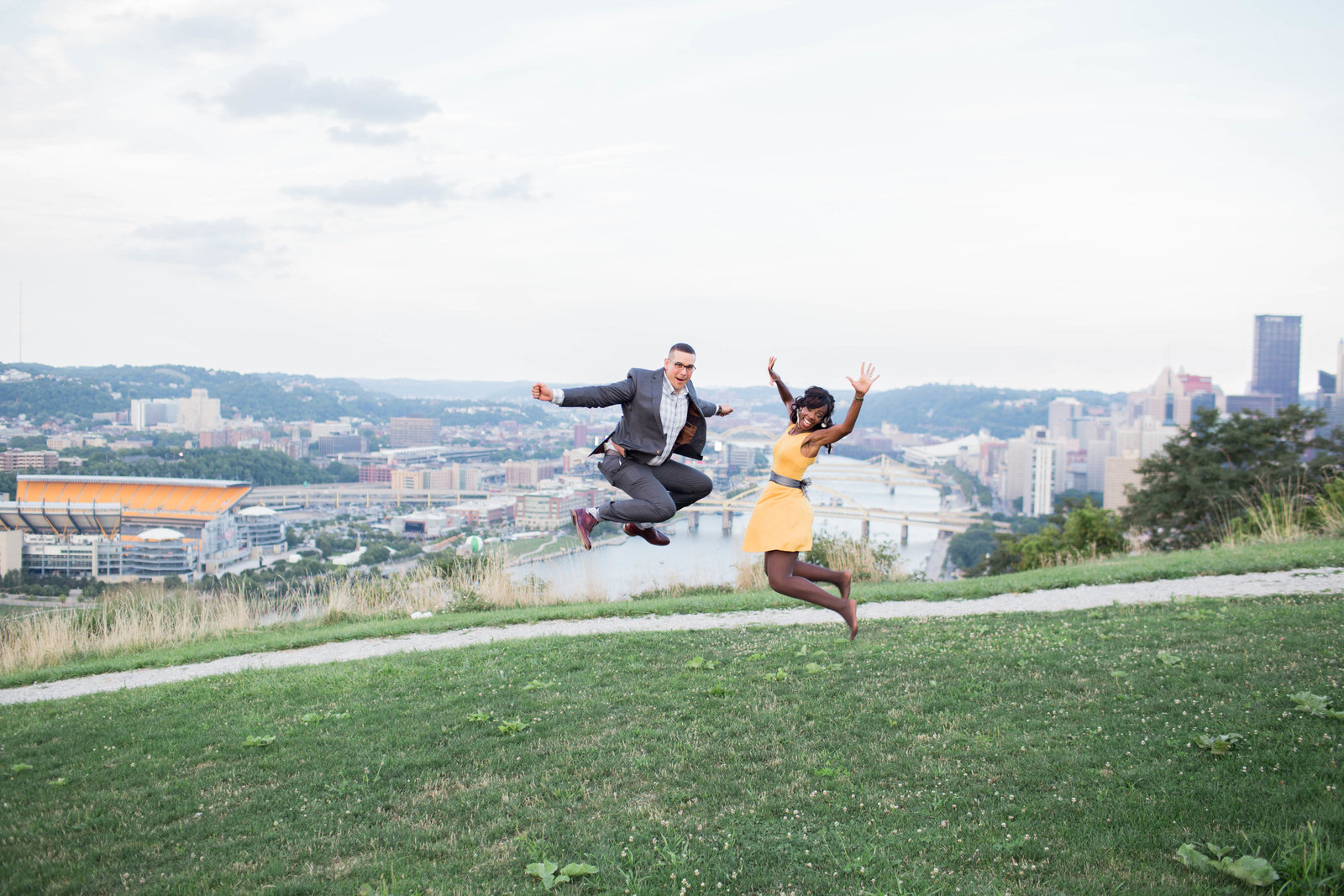 couple jump high in the air on mount washington with pittsburgh in the background
