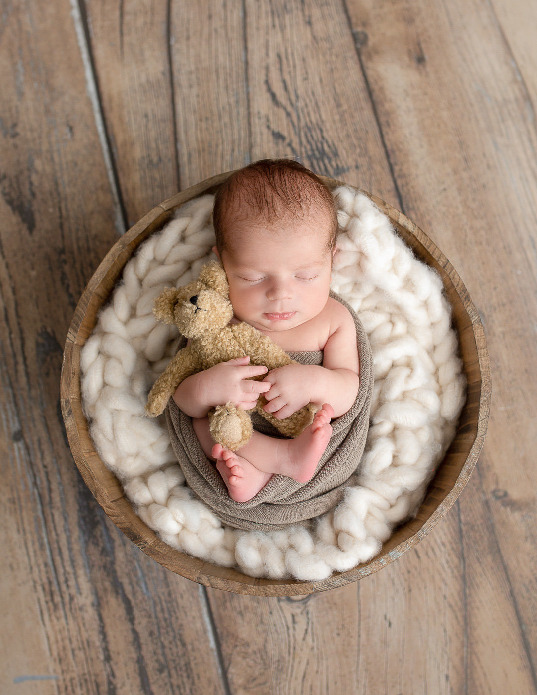 Cute newborn boy posed in a bowl in our in home Rochester NY studio.