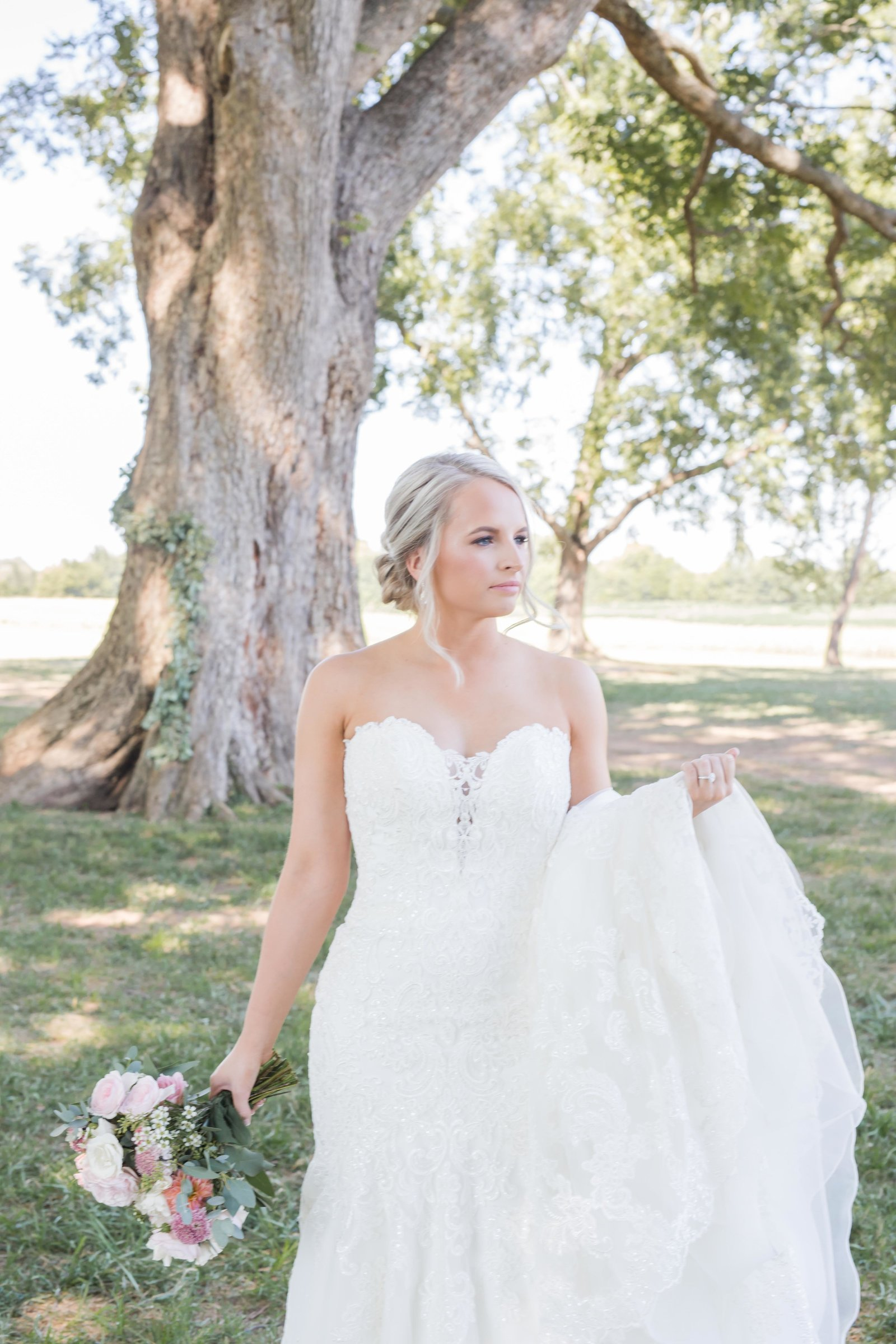 blonde bride holding wedding gown and bridal bouquet