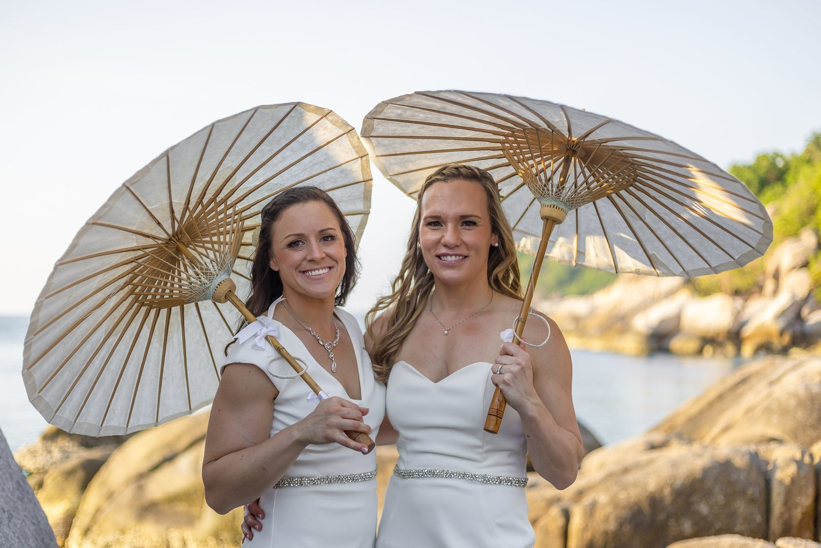 brides on beach with parasol