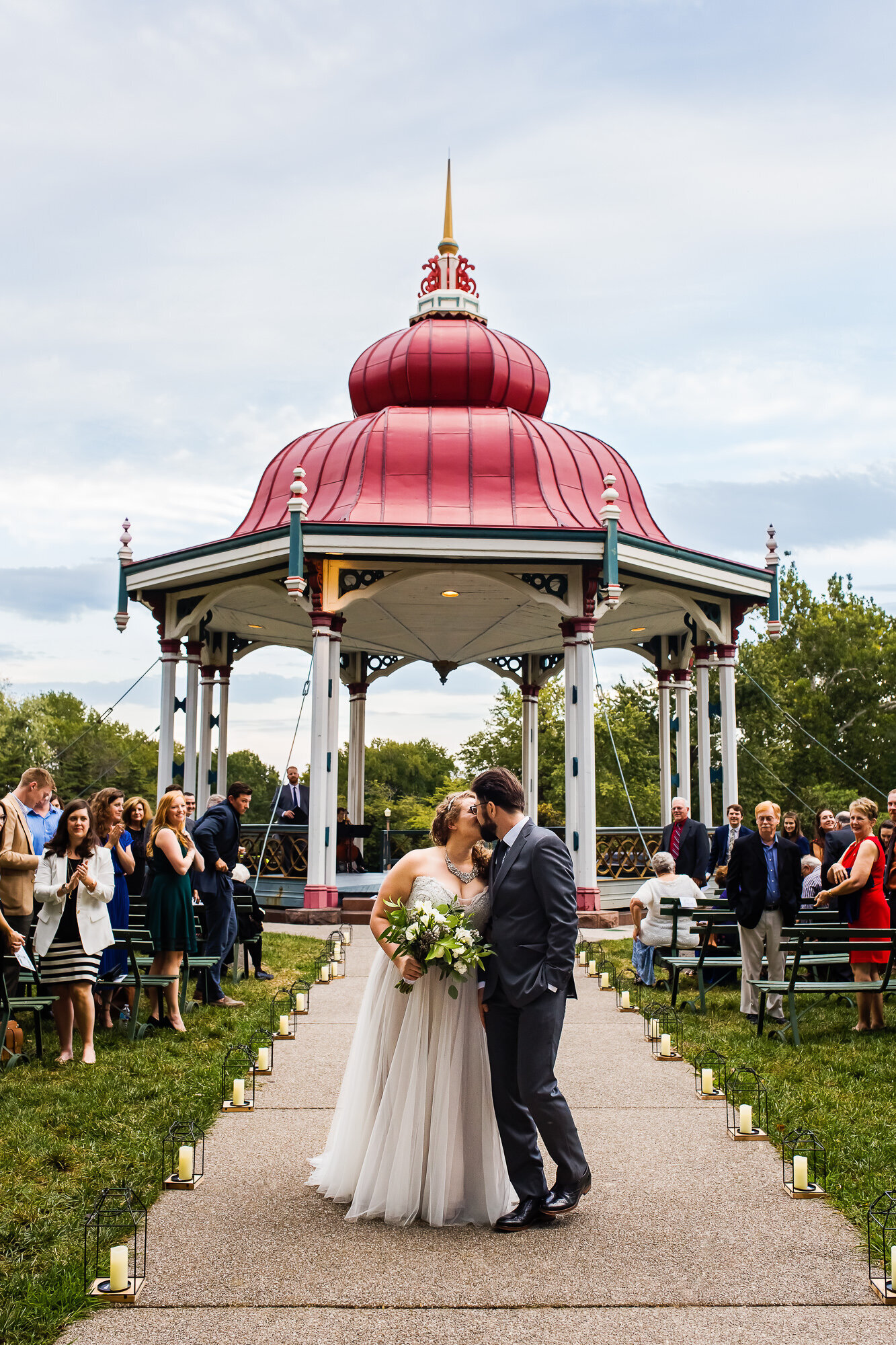 Bride and groom kiss as they walk back down the aisle after getting married in Tower Grove Park at The Music Stand