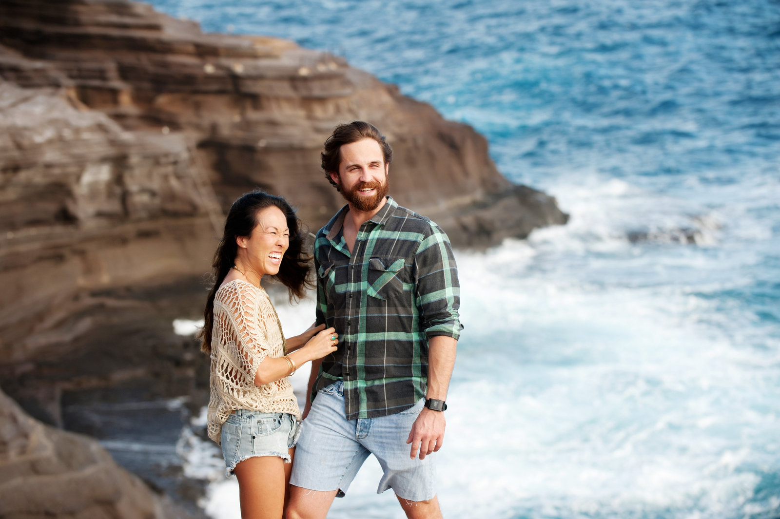 a couple strike a pose and laugh on a cliff in front of the bright blue ocean in honolulu