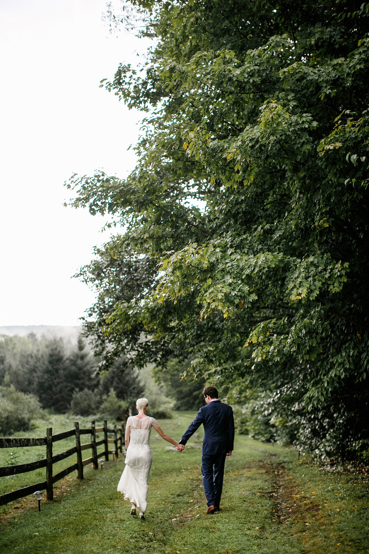 bride and groom walking down tree covered farm path