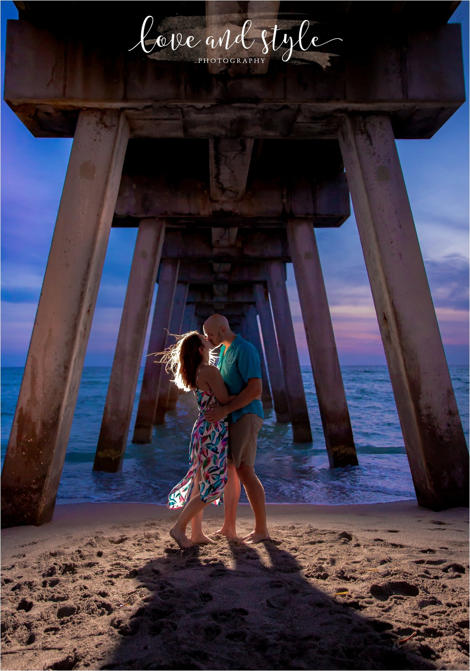 Engagement Photography on Venice Dog Beach under the pier with backlight and couple kissing