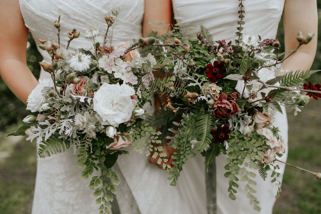 Same sex brides holding bouquets